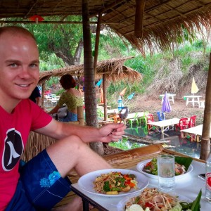 Eating some spicy som tam, by the creek, under bungalow, in the rain.